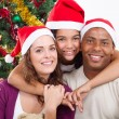 Happy family sitting near Christmas tree — Stock Photo