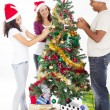 Happy multiracial family decorating Christmas tree — Stock fotografie