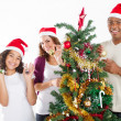 Happy multiracial family decorating Christmas tree — 图库照片