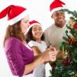 Happy multiracial family decorating Christmas tree - Zdjęcie stockowe