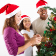 Happy multiracial family decorating Christmas tree - Stock Photo