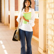 Stock Photo: Cute female college student in school building