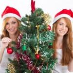 Beautiful twin sisters decorating Christmas tree — Stock Photo