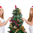 Happy teen sisters decorating Christmas tree — Stock Photo #11308966