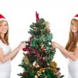 Happy teen sisters decorating Christmas tree — Stock Photo