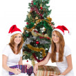Stock Photo: Happy young sisters sitting under christmas tree