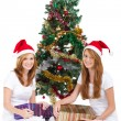 Happy young sisters sitting under christmas tree — Stock Photo