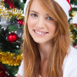Beautiful teen girl in front of a Christmas tree - Photo