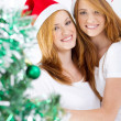 Happy young friends behind Christmas tree — Stock Photo