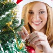 Happy beautiful woman decorating christmas tree — Stok fotoğraf