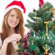 Teen girl decorating a Christmas tree — Stok fotoğraf