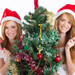Teen sisters holding candy cane behind a Christmas tree - Stock Photo