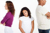 Unhappy girl standing between divorcing father and mother — 图库照片