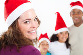 Multiracial family of four wearing santa hats on white — Stock Photo