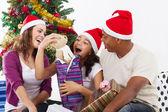 Lycklig familj öppnar julklapp hemma — Stockfoto
