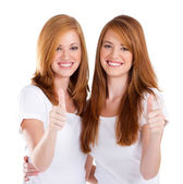 Happy teen sisters giving thumbs up — Stock Photo
