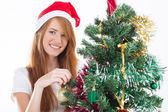 Teen girl decorating a Christmas tree — Stock Photo