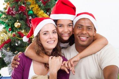 Happy family sitting near Christmas tree