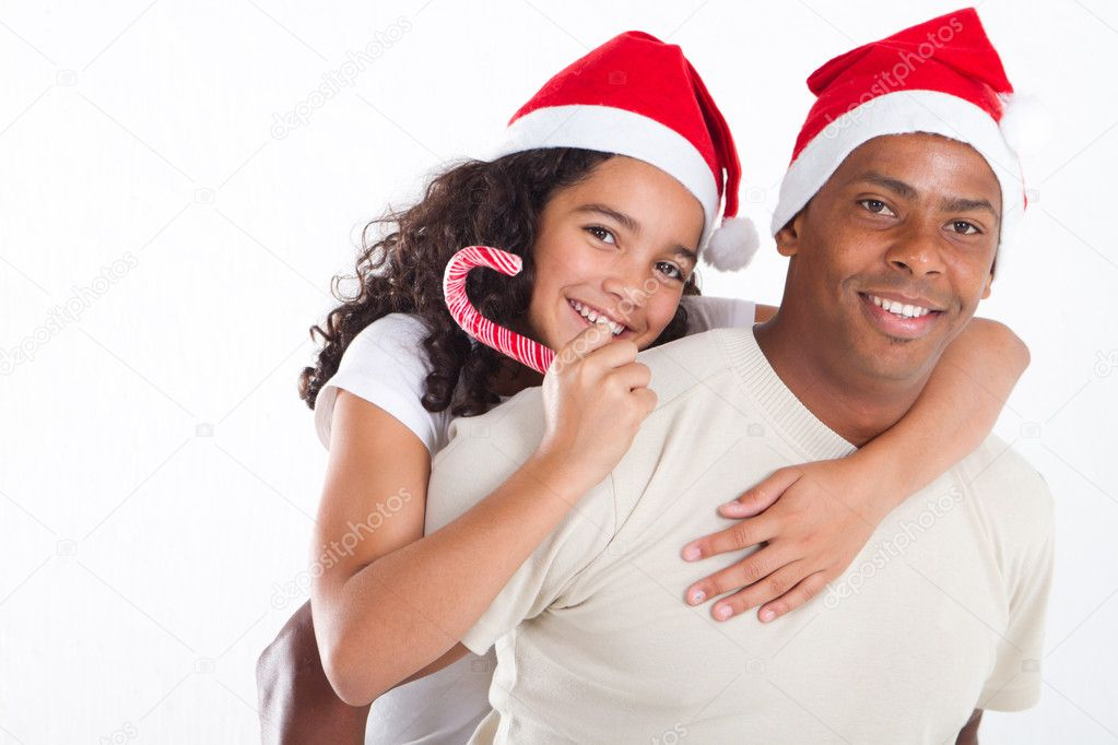 Happy father carrying daughter on his back with Christmas hat — Stock Photo #11308058