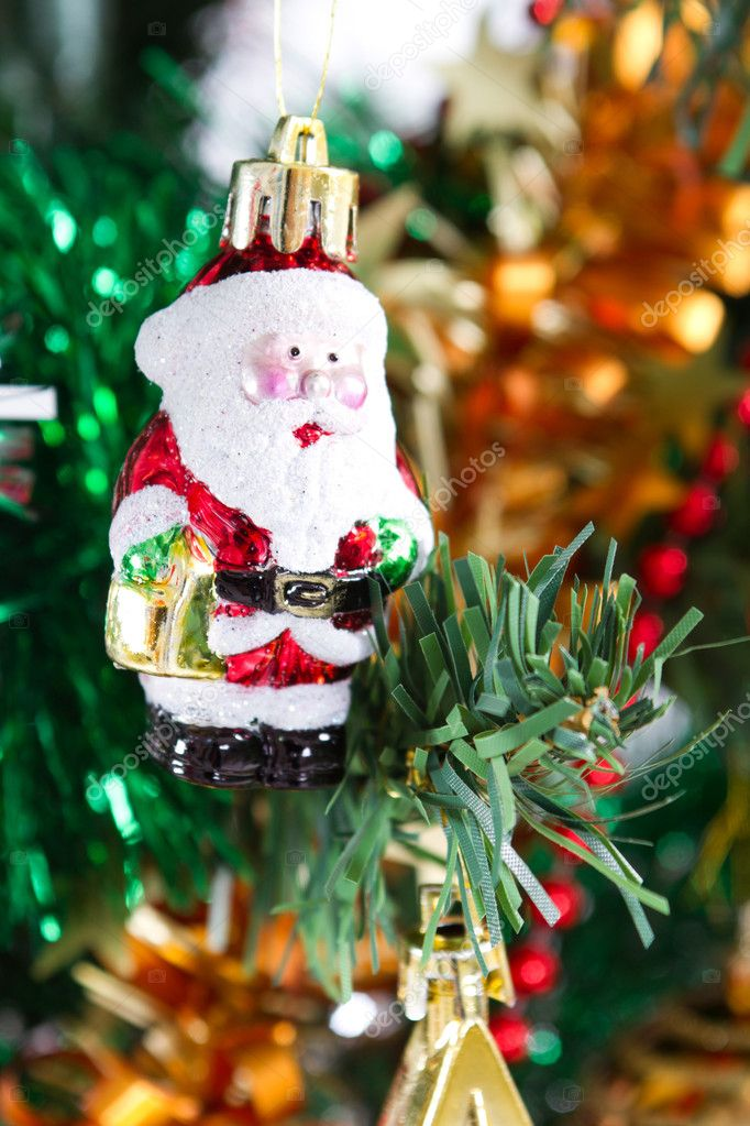 Little santa claus ornament hanging on christmas tree — Photo #11308119