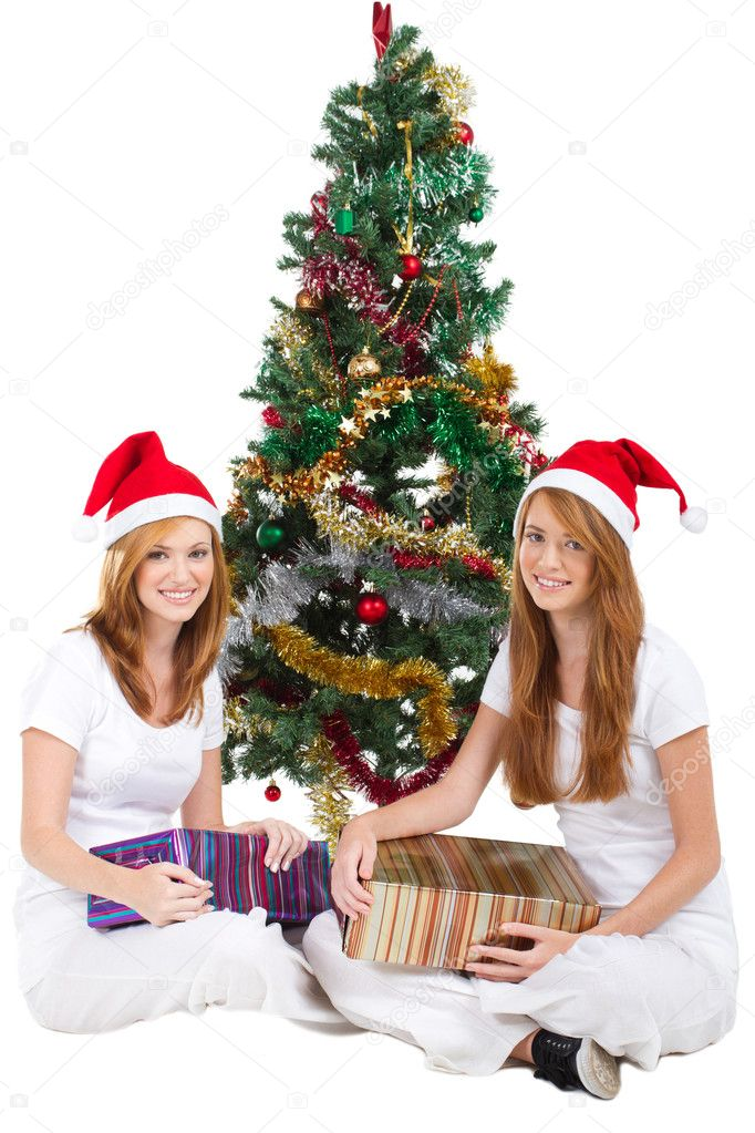 Happy young sisters sitting under christmas tree holding gifts  Stock Photo #11308971