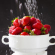 Water pouring on bowl of strawberries - Stock Photo