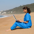 Young female doctor using laptop on beach — Stock Photo
