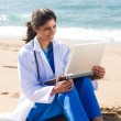 Stock Photo: Young female doctor working on laptop on beach