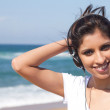 Young Arabian woman listening music on beach — Stock Photo #11339192