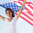 Happy young woman holding american flag — Stock Photo #11339265