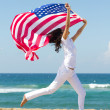 Stock Photo: Young active womholding americflag