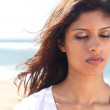 Thoughtful young indian woman with eyes closed on beach — Stock Photo #11339318