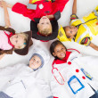 Group of kids in various uniforms lying on floor — Stock Photo