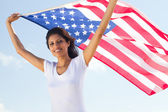 Happy young woman holding american flag — Stock Photo
