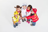 Overhead view of kids in occupational uniforms teamwork — Stock Photo