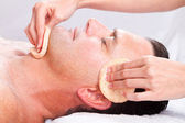 Middle age man receiving facial massage — Stok fotoğraf