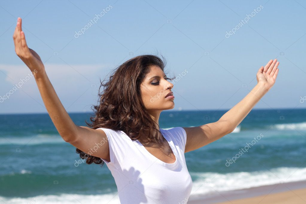 Young attractive woman praying on beach  Stock Photo #11339154