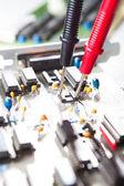 Multimeter examining a circuit board — Stock Photo