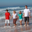 Family walking on beach — Stock Photo