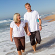 Middle aged couple walking on beach — Stock Photo