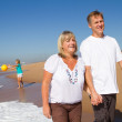 Happy mid age couple teen kids walking on beach — Stock Photo #11363731