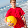 Teen boy with beach ball on beach — Stock Photo