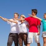 Family of four posing on blue sky — Stock Photo