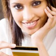 Beautiful young woman holding a credit card and smiling — Stock Photo
