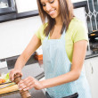 Pretty woman cooking at home kitchen — Stock Photo