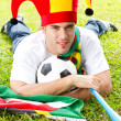 Soccer fan lying on green grass — Stock Photo