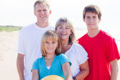 Family of four on beach — Stock Photo