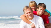 Middle aged father and teen kids on beach — Stock Photo