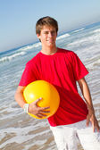 Teen boy with beach ball on beach — Stock Photo
