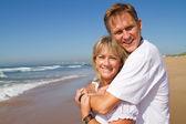 Happy loving mature couple on beach — Stock Photo